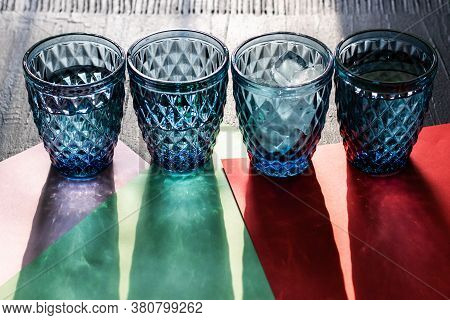 Set Of Four Patterned Blue Glasses Of Water With Ice Or Cocktails With Long Shadows On Colorful Pape