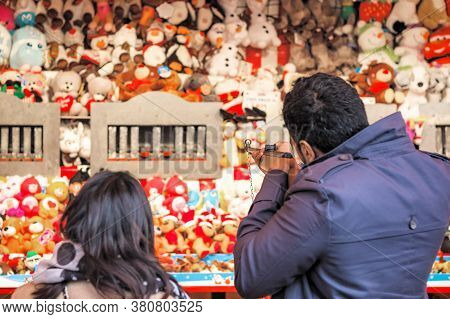 Back View Of Tourists Playing Shooting Game To Win Plush Toys On The Wall At Christmas Funfair Winte