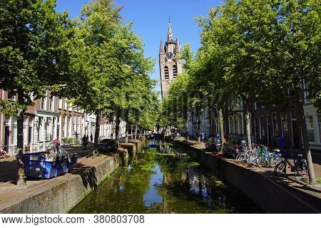 Delft, The Netherlands - August 5, 2020: The Oude Delft Canal And Leaning Tower Of Gothic Protestant