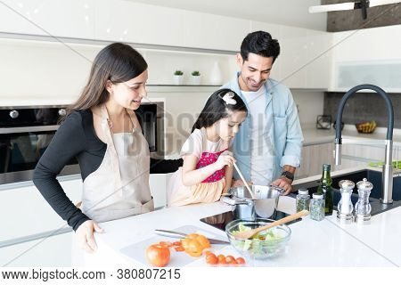 Smiling Latin Family Looking At Daughter Cooking Food In Kitchen
