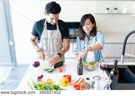 Young Latin Couple Making Vegetable Salad In Kitchen At Home