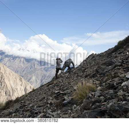 Hunters In The Mountains Creep Up The Steep Slope To The Captured Animals. Two Men With Guns And Bin