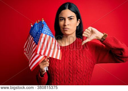 Young beautiful hispanic woman holding United States of American flag at independence day with angry face, negative sign showing dislike with thumbs down, rejection concept