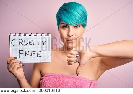 Young woman with blue fashion hair showing cruelty-free cosmetics message with angry face, negative sign showing dislike with thumbs down, rejection concept
