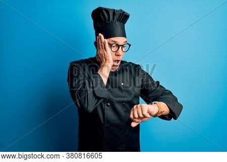 Middle age handsome grey-haired chef man wearing cooker uniform and hat Looking at the watch time worried, afraid of getting late