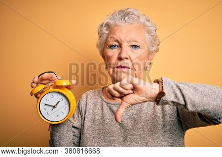 Senior beautiful woman holding alarm clock standing over isolated yellow background with angry face, negative sign showing dislike with thumbs down, rejection concept