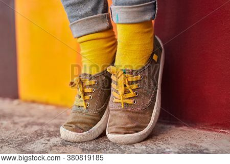 Unrecognizable Female Hipster In Cloth Shoes And Bright Yellow Socks Standing On Tips Of Toes Near W