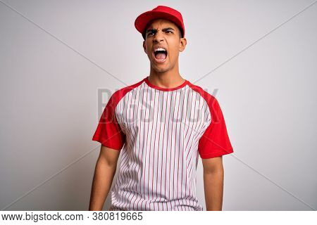 Young handsome african american sportsman wearing striped baseball t-shirt and cap angry and mad screaming frustrated and furious, shouting with anger. Rage and aggressive concept.