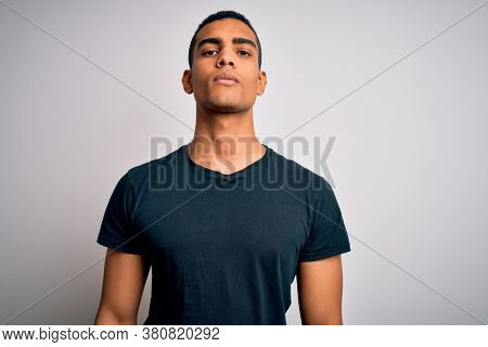 Young handsome african american man wearing casual t-shirt standing over white background Relaxed with serious expression on face. Simple and natural looking at the camera.