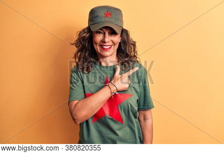 Middle age brunette woman wearing t-shirt and cap with red star symbol of communism smiling cheerful pointing with hand and finger up to the side