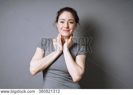 Happy Young Woman With A Satisfied Smile On Her Face Against Gray Background With Copy Space