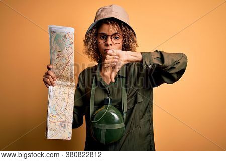 African american tourist woman wearing explorer hat and water canteen holding city map with angry face, negative sign showing dislike with thumbs down, rejection concept