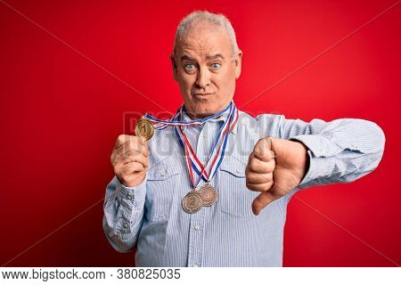 Middle age hoary champion man wearing medals standing over isolated red background with angry face, negative sign showing dislike with thumbs down, rejection concept