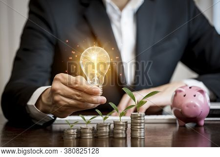 Businessman Hand Holding Light Bulb And Leaf On  Coins Stack On The Wooden Table , Saving Ideas And