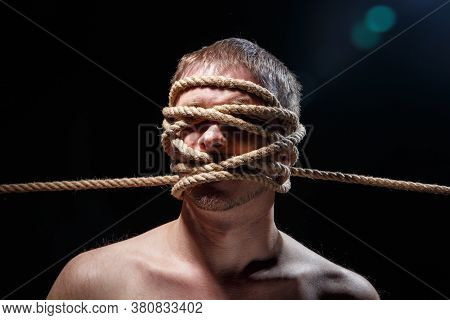 Photo Of Binded Scary Man With Rope On Face