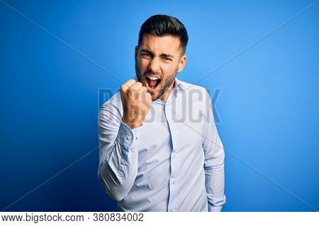 Young handsome man wearing elegant shirt standing over isolated blue background angry and mad raising fist frustrated and furious while shouting with anger. Rage and aggressive concept.
