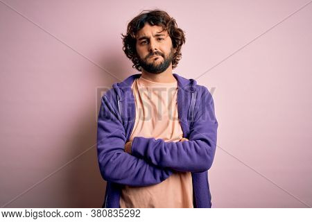 Young handsome sporty man with beard wearing casual sweatshirt over pink background skeptic and nervous, disapproving expression on face with crossed arms. Negative person.