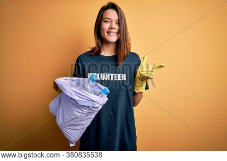 Beautiful volunteer girl caring environment doing volunteering holding bag with rubish bottles very happy pointing with hand and finger to the side