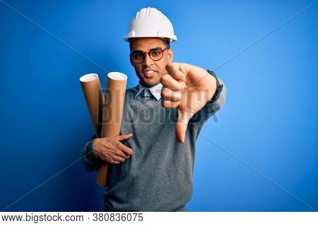 Young african american afro architect man wearing safety helmet holding bluprints with angry face, negative sign showing dislike with thumbs down, rejection concept