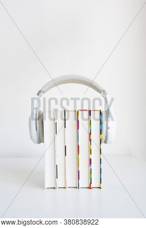 White Headphones On A Stack Of 5 Book On A Table Against A White Wall Background. Audiobook Concept.