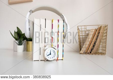 White Headphones On A Stack Of 5 Book, A Small Alarm Clock, A Basket Of Books And Indoor Flowers On