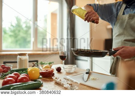 Cropped Shot Of Man, Cook In Apron Pouring Oil On The Pan For Preparing Dinner, Standing In The Kitc