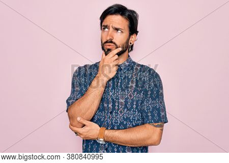 Young handsome hispanic bohemian man wearing hippie style over pink background Thinking worried about a question, concerned and nervous with hand on chin