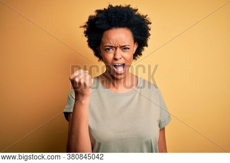 Young beautiful African American afro woman with curly hair wearing casual t-shirt angry and mad raising fist frustrated and furious while shouting with anger. Rage and aggressive concept.