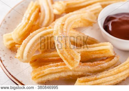 Churros With Powdered Sugar And Chocolate Sauce
