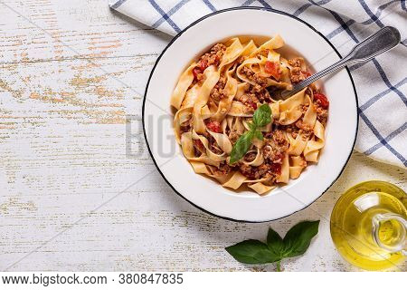 Traditional Italian Pasta Bolognese On A White Plate On A Wooden Background