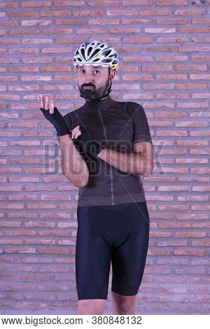 Humorous Young Male Cyclist Putting His Mittens On With A Playful Seductive Look