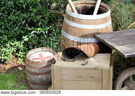 Old Rustic Antique Wooden Barrels, Box And Cart In Medieval Setting