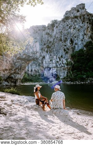 Couple On The Beach By The River In The Ardeche France Pont D Arc, Ardeche France, View Of Narural A