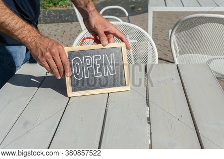 Handwritten Open Sign In Hands Of Waiter On Cafe Table Outside. Hands Holding Signboard Open In Open
