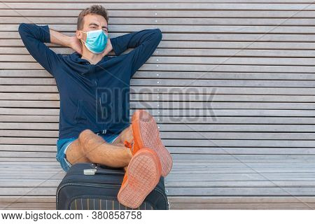 Man In Medical Mask Sitting On Bench With Luggage And Waiting. Traveler Wearing Protective Mask With