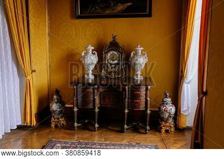 Castle Interior. Chest Of Drawers With Brass Inlay, Chinese Porcelain Vases And Antique Clock. Milot