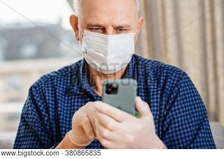 Paris, France - March 26, 2020: Close-up Of Curious Senior Man Using Protective Gloves And Surgical
