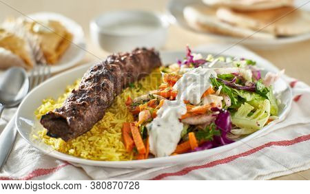 greek beef souvlaki platter with rice and pickled vegetables covered in tzatziki sauce