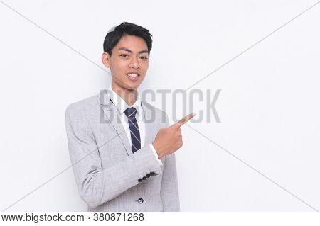 young handsome businessman wearing in gray suit ,tie with white shirt with pointing finger to side
