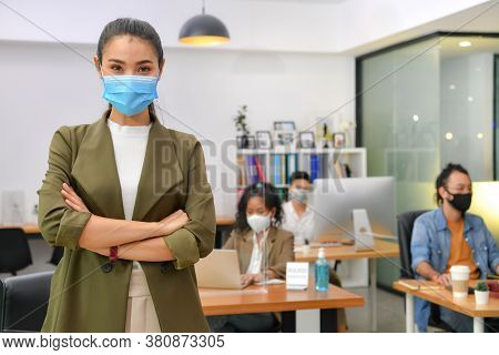 Asian Woman Wearing Face Mask Smile And Looking At Camera Working In New Normal Office And Doing Soc
