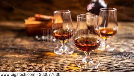 Caribbean Rum In Modern Glasses With A Bottle Of Rum And A Cigar In The Background.