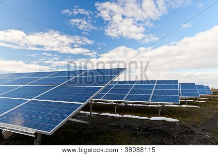 Solar photovoltaics panels field for renewable energy production with blue sky and clouds poster