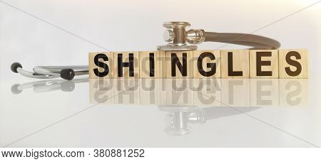 Shingles The Word On Wooden Cubes, Cubes Stand On A Reflective White Surface, On Cubes - A Stethosco