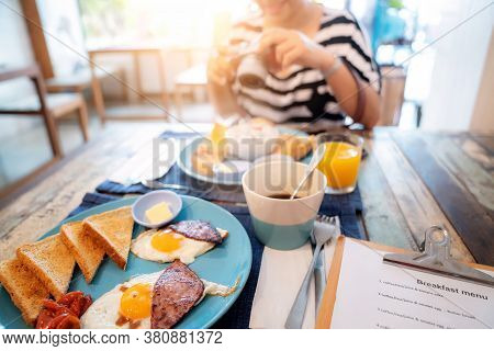 Woman Guest Enjoy Her Breakfast Manu In Restaurant Inside Her Hotel, This Image Can Use For Food, Ho