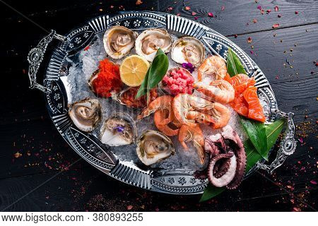 Assorted Seafood, Shrimp, Scallops, Squid, Mussels. Serving Plates On The Table With A Set Of Seafoo