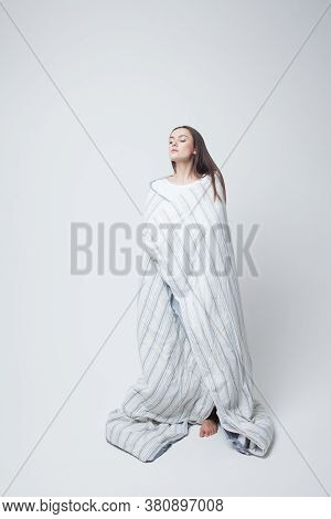 Healthy Sleep And Drowsiness, Beautiful Young Woman Standing Wrapped In A Blanket, Light Gray Backgr