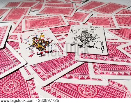 Bosnia And Herzegovina - April 9, 2020: Two Jokers From A Deck Of Playing Cards On A Pile Of Cards W