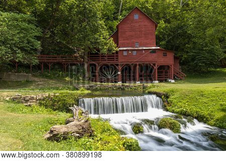 An Old Red Grist Mill With A Small Waterfall.