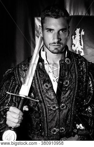 Portrait Of Handsome King With Beard Dressed In Costume Holding A Sword And Looking At Camera