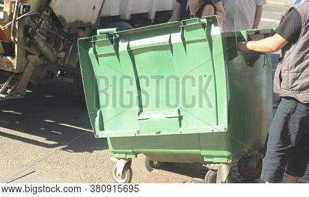 Dustman Worker Is Moving Empty Garbage Container From Truck.